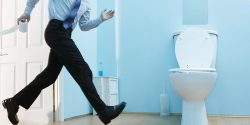 Male executive running to toilet